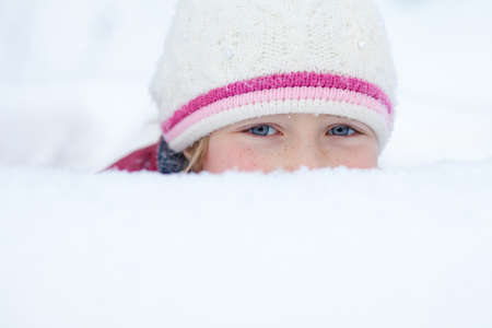 little girl look out of snowdrift with smiley eyes Stock Photo - 8340193