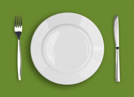 ustensiles de cuisine: Fourche sur fond vert, la plaque blanche et le couteau