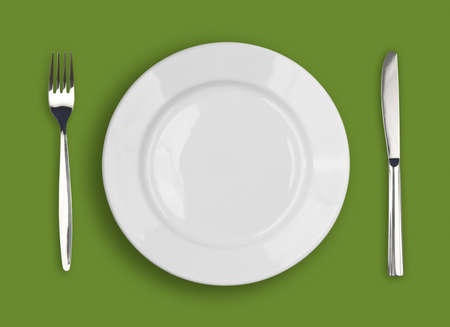 plate setting: Knife, white plate and fork on green background