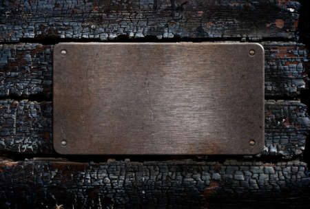 scorched: metal plate over burned wooden background