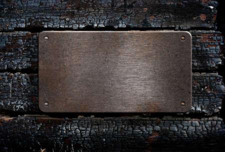 quemado: placa de metal sobre fondo de madera quemada Foto de archivo