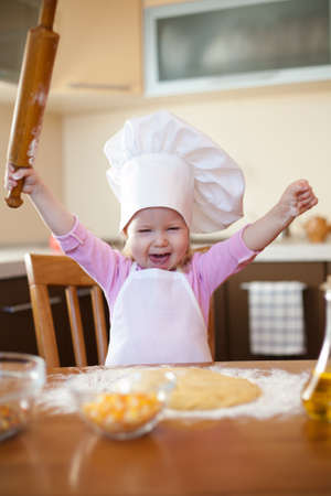 Little girl makes dough on kitchen with rolling pin photo