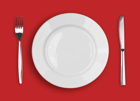 Knife, white plate and fork on red background photo
