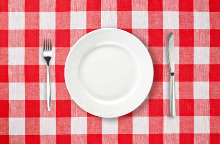 checked fabric: white plate on red checked tablecloth Stock Photo