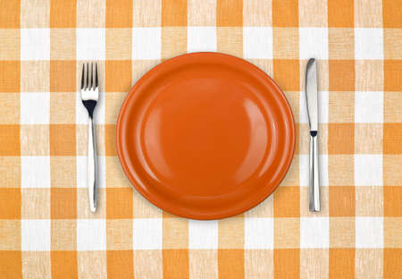 Knife, orange plate and fork on yellow checked tablecloth photo