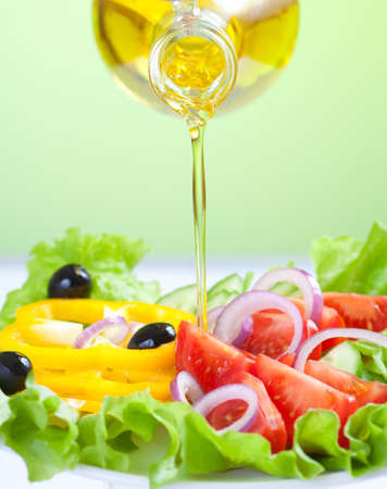 oil: sunflower seed oil stream and healthy fresh vegetable salad