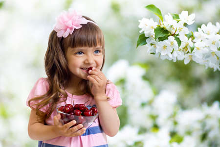little girl with cherry berries bowl in studio isolated photo