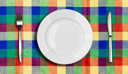 Knife, plate and fork on multicolor checked tablecloth photo