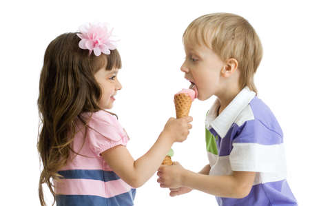 gives: girl shares, gives or feeds boy with her ice cream in studio isolated