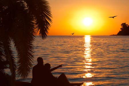 Loving couple watching beautiful sunset on seashore photo