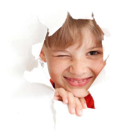 funny kid mit Augenzwinkern Auge Porträt in zerrissenes Papier Loch isoliert