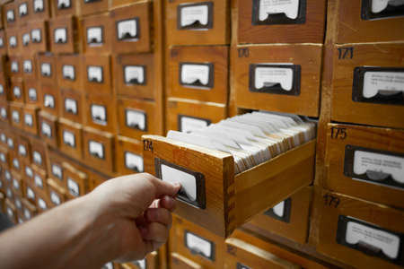 index card: database concept. vintage cabinet. human hand opens library card or file catalog box.