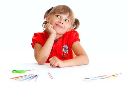 dessin enfants: Schoolgirl est assis à table avec des crayons, des peintures et des ciseaux isolés