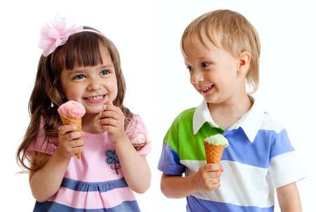 comiendo helado: feliz hijos gemelos chica y chico con helado en estudio aislado Foto de archivo