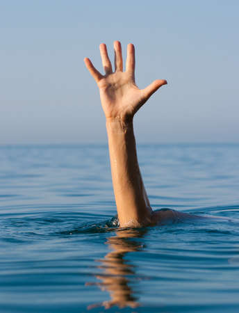 reach: single hand of drowning man in sea asking for help