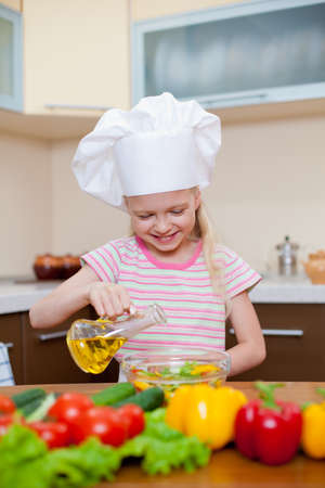 Little girl with oil preparing healthy food on kitchen Stock Photo - 10525932