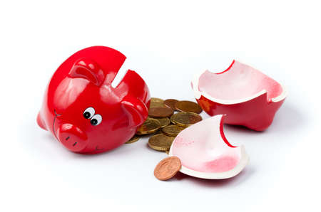 penury: Broken piggy bank or money box with coins isolated on white