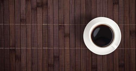 placemat: Tazza caff� vista superiore sul tavolo di bamb� Archivio Fotografico