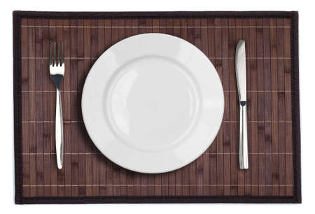 Bamboo placemat with plate fork and knife isolated on white photo