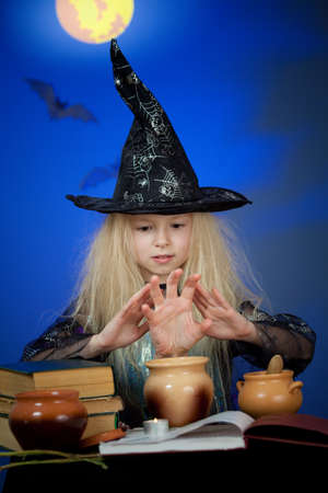 Girl dressed up as witch in night making magic photo