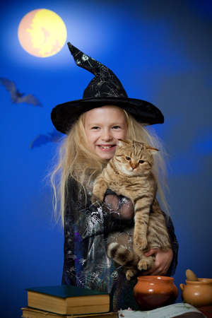 Girl dressed up as witch in night with cat photo