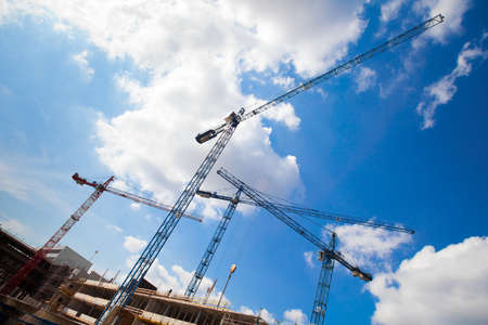 bilding: construction cranes and unfinished house against the blue sky with clouds Stock Photo