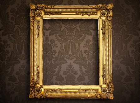 Empty golden painting frame on vintage wallpaper photo