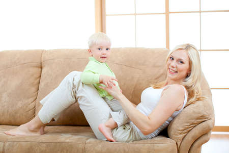 Happy son and mother lying on sofa looking directly to camera. photo