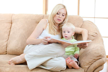 Happy son and mother lying on sofa looking directly to camera. Stock Photo - 10938154