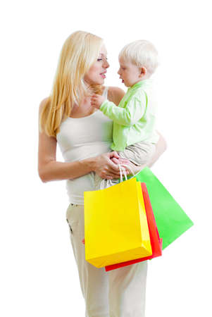 blonde mom: Standing mother with son and colorful paper shopping bag isolated on white Stock Photo
