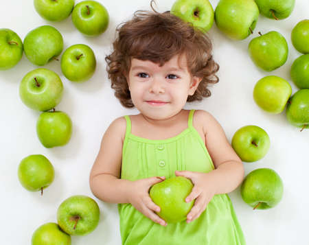 Adorable little girl lying with green apples photo