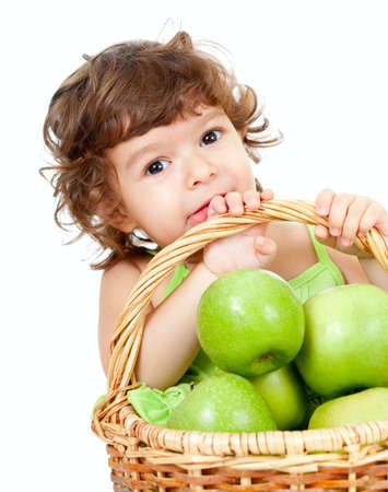 curly headed: Adorable little girl with green apples in basket isolated studio shot