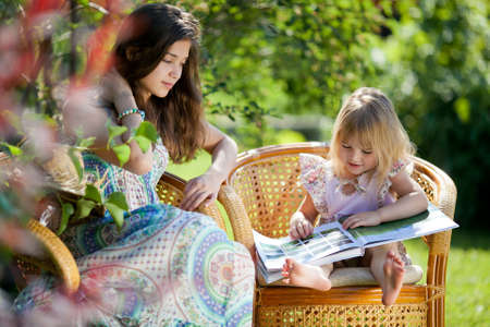 Girls reading book sitting in wicker chairs outdoor in summer day photo