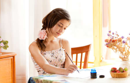 girl writing at table by pen and ink indoor in summer day with strawberries Stock Photo - 11124609