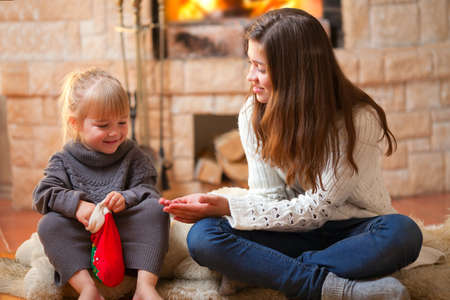 Two girls sitting fireside and opening christmas presents photo