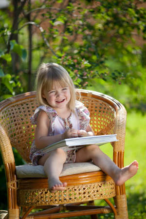 Little girl reading book sitting in wicker chair outdoor in summer day photo