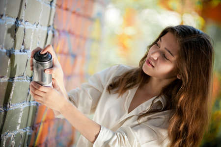 teenage girl portrait with spray can near graffiti wall photo