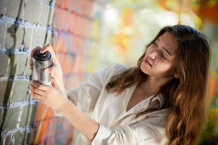 teenage girl portrait with spray can near graffiti wall