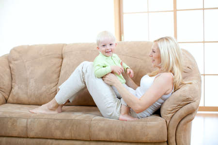 play room: Happy son and mother playing on sofa
