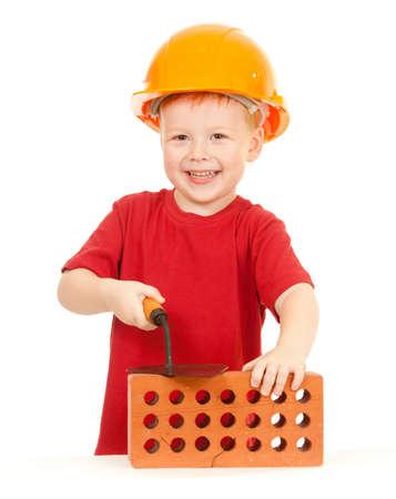 casco rojo: Niño en casco con la paleta y el ladrillo aislado