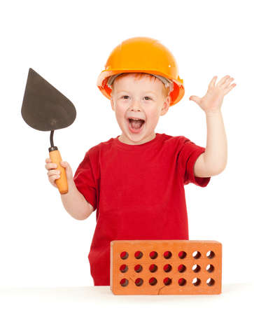Boy in hard hat with trowel and brick isolated photo