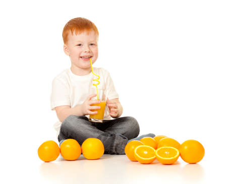 red-haired boy with ornage juice and oranges isolated on white photo