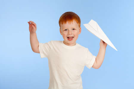 Adorable red-haired boy with paper plane model on blue background in studio photo