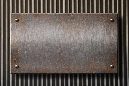 hard alloy: grunge rusty metal plate over grid background
