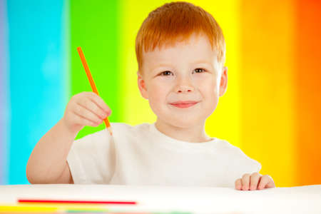 Red-haired adorable boy drawing with orange pencil on rainbow background photo