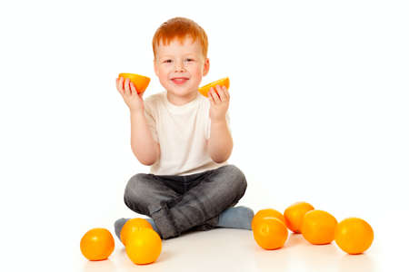 redheaded boy with oranges isolated on white photo