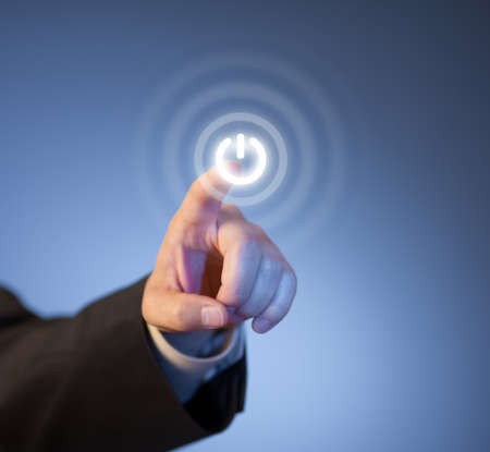 enter button: Mans finger pressing virtual power button on touch screen