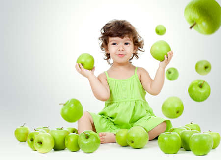 only: Adorable little girl sitting among falling green apples