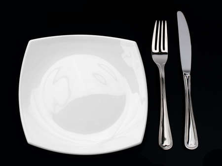 Knife, square white plate and fork on black background photo