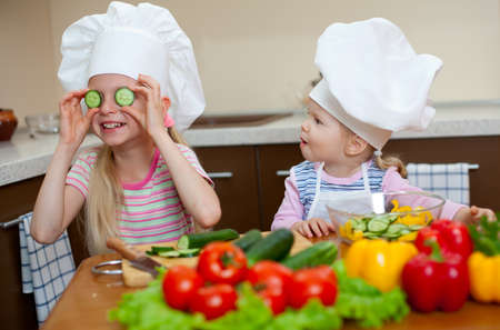 two little girls preparing healthy food on kitchen photo